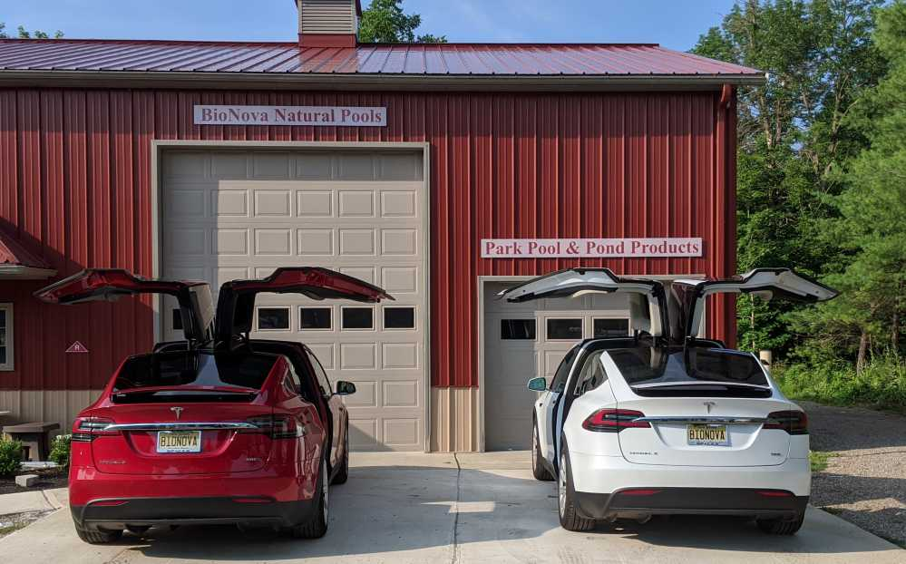 Image of two Tesla model X's in front of one of BioNova's warehouses
